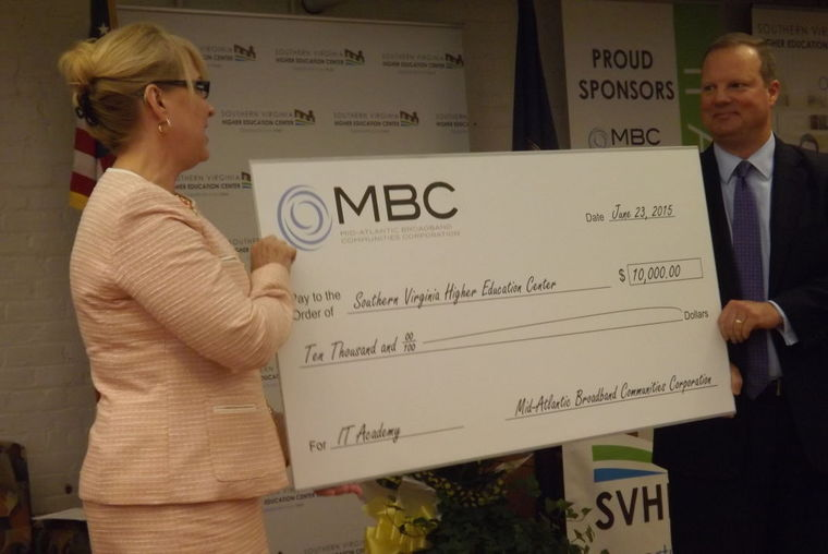 Southern Virginia Higher Education Center Executive Director Dr. Betty H. Adams accepts a $10,000 check from Mid-Atlantic Broadband Communities Corporation President and CEO Tad Deriso that will go toward scholarships for students attending the IT Academy.